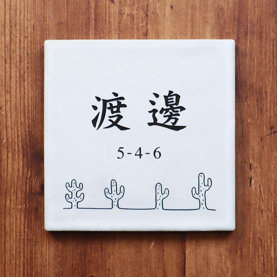 漢字が引き立つカッコいいデザインのタイル表札を木目の壁に設置して撮影した写真